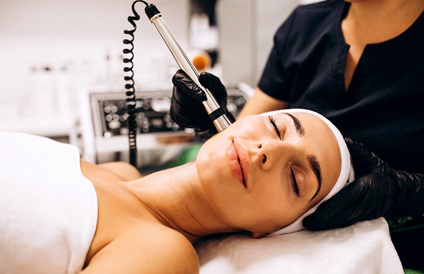 یک خانم با هدبند سفید روی تخت و پزشک با لباس مشکی بالا سر او